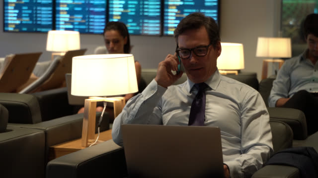 erwachsener geschäftsmann in der vip-flughafen-lounge arbeitet am laptop und erhält einen anruf - wartehalle stock-videos und b-roll-filmmaterial