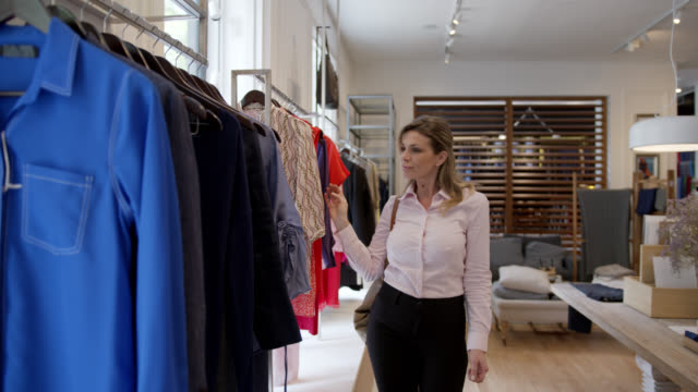 adult business woman at a women's boutique looking at a shirt she liked on hanger - decisions stock videos & royalty-free footage