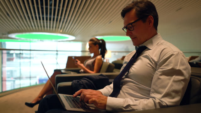 adult businessman working on his laptop at the vip lounge in the airport - gate stock videos & royalty-free footage