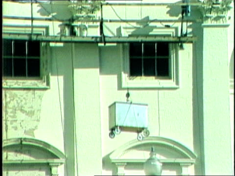 stockvideo's en b-roll-footage met adult caucasian male laborer lowers a box from the side of the us capitol building with a winch during renovations adult caucasian male worker... - neoklassiek