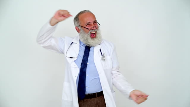Adult cheerful senior doctor smiling and happy dancing on a gray background