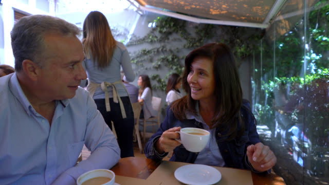 Adult couple at a restaurant enjoying a coffee and talking having a nice time