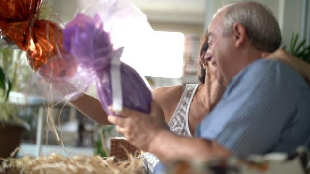 coppia adulta che celebra la pasqua brasiliana con uova di cioccolato - uovo alimento di base video stock e b–roll