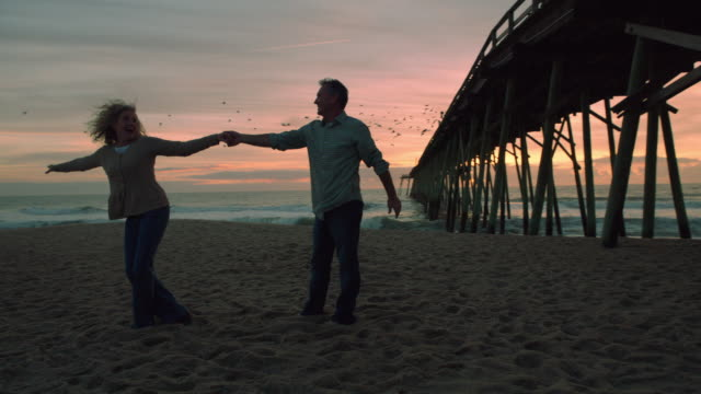 Adult couple dancing in front of sunset beach as birds fly away (slo-mo)