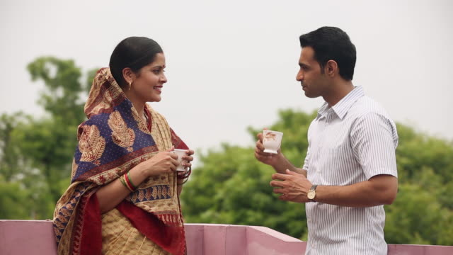 adult couple drinking tea at roof top - indian couple tea stock videos & royalty-free footage