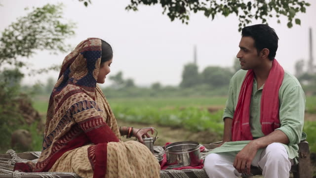 Adult couple eating lunch in the farms, Haryana, India