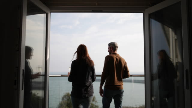 adult couple enjoying view from balcony of sea - balcony stock videos and b-roll footage