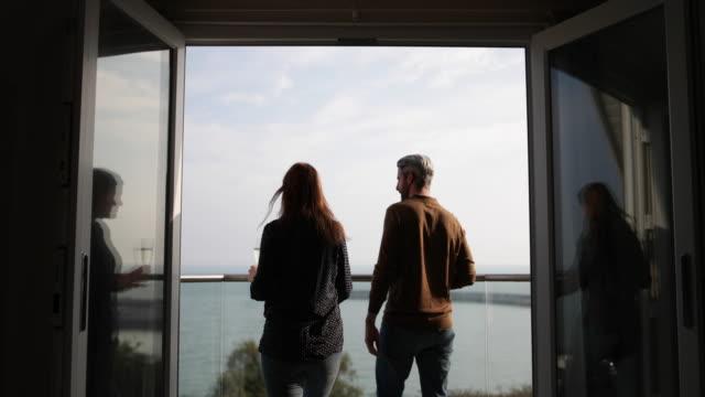 stockvideo's en b-roll-footage met adult couple enjoying view from balcony of sea - balkon