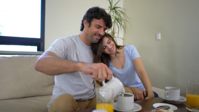 Adult couple having breakfast at their hotel room and man serving milk in their coffee and woman cuddling next to him smiling