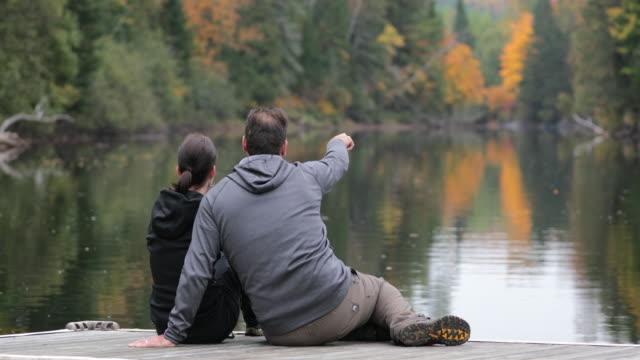 vídeos de stock e filmes b-roll de adult couple having fun on wooden dock in autumn - docas