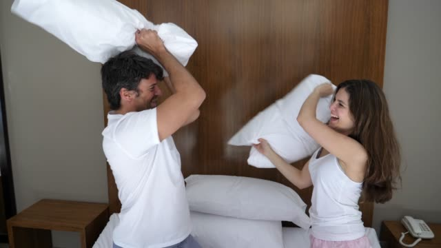 Adult couple having fun pillow fighting on their bed laughing and smiling