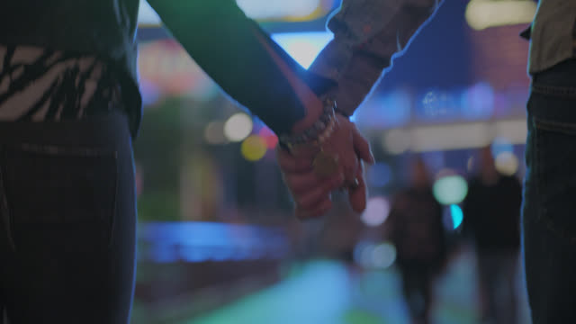 Adult couple hold hands and wrap arms around each other as they walk on night out in Las Vegas.