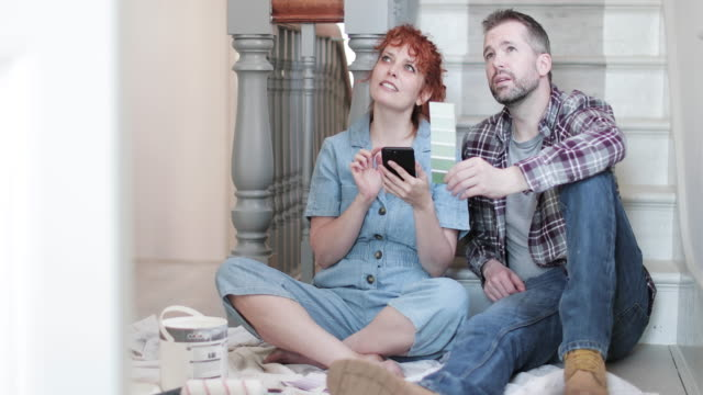 adult couple in new home looking at decorating ideas on smart phone - decoration stock videos & royalty-free footage