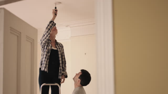 Adult Couple installing smoke alarm in home