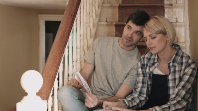 adult couple looking at colour swatch on staircase in new home - choosing stock videos & royalty-free footage