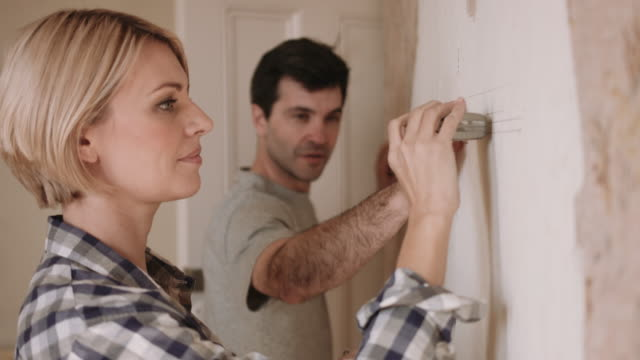 Adult couple measuring wall in new home