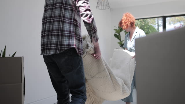 adult couple moving into new home and putting down carpet - blooper film clip stock videos & royalty-free footage