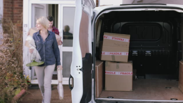 adult couple moving out of home with boxes and homeware - van stock videos & royalty-free footage