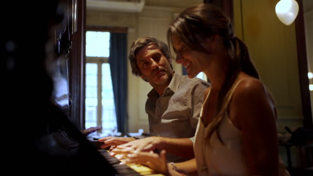 adult couple playing a piano together - gratitude stock videos & royalty-free footage