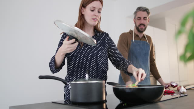 Adult Couple preparing a meal together in kitchen