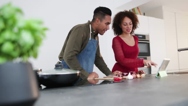 adult couple preparing a meal together in kitchen - kochrezept stock-videos und b-roll-filmmaterial