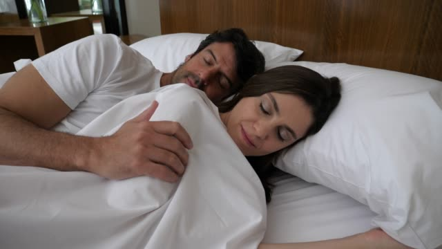 Adult couple sleeping in bed and man cuddling behind his partner hugging her very sweetly