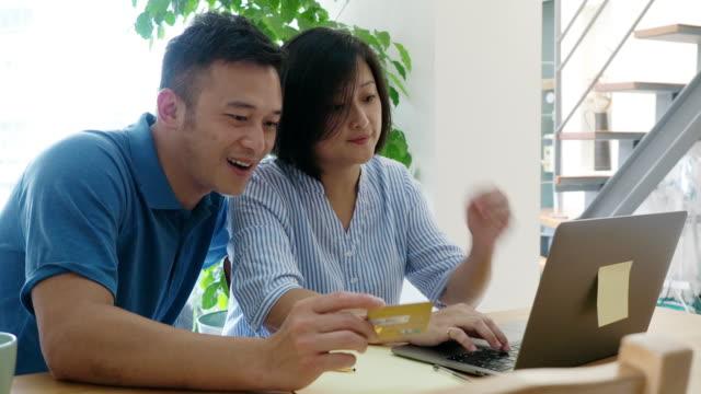 vidéos et rushes de couples adultes surfant sur le filet ensemble à la maison avec l'ordinateur portatif - âge humain