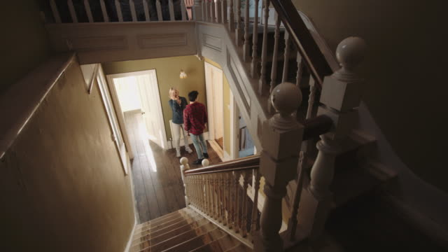 adult couple viewing home for sale - staircase stock-videos und b-roll-filmmaterial