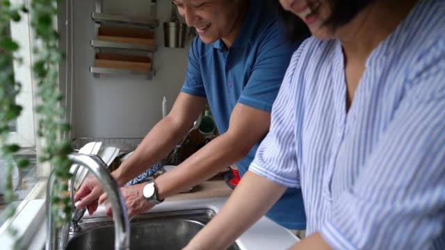 vídeos de stock, filmes e b-roll de os pares adultos que lavam pratos junto na cozinha em casa - louça