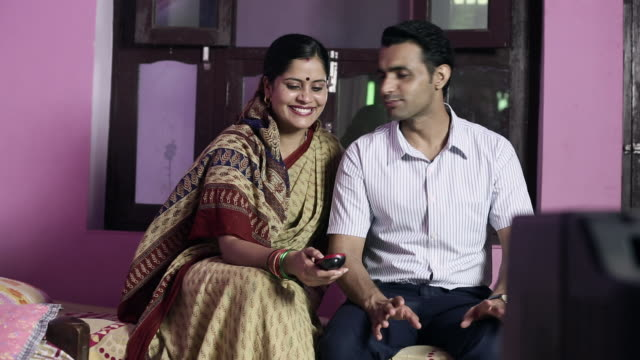 vidéos et rushes de adult couple watching television in the home - indien d'inde