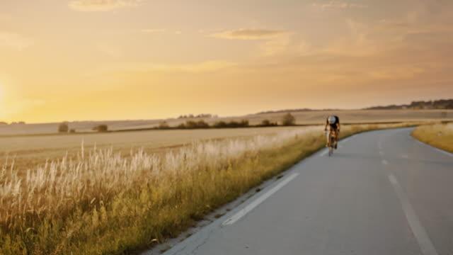 vídeos de stock e filmes b-roll de slo mo adult cyclist driving fast through the countryside at sunset - bicicleta de corrida