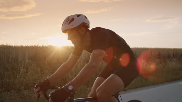 slo mo adult cyclist riding a bike through the countryside at sunset - active lifestyle stock videos & royalty-free footage