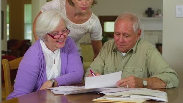 stockvideo's en b-roll-footage met ms adult daughter assisting senior couple doing paperwork, austin, texas, usa - financial bill