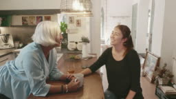 Adult Daughter Laughing with Mother in Family Kitchen