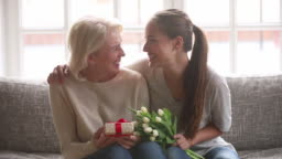 Adult daughter presenting flowers and gift box to old mother