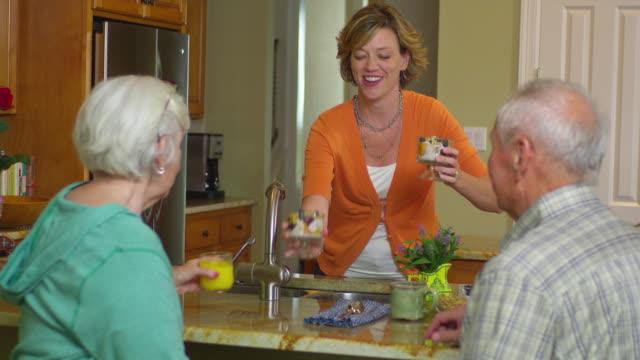 stockvideo's en b-roll-footage met ms adult daughter serving desserts to parents in kitchen, austin, texas, usa - man met een groep vrouwen