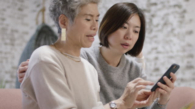 Adult Daughter Teaching Her Mother How to Use A Cell Phone