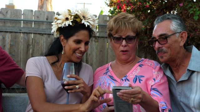 ms adult family members laughing at video on smart phone during backyard barbecue - older woman fun stock-videos und b-roll-filmmaterial