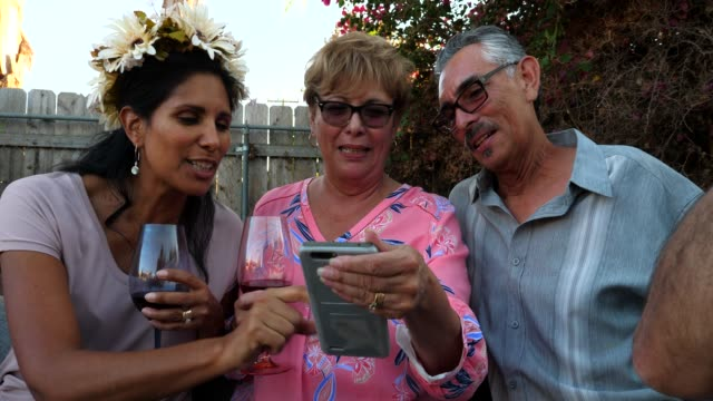 ms adult family members looking at photo on smart phone during backyard barbecue - frauen über 40 stock-videos und b-roll-filmmaterial