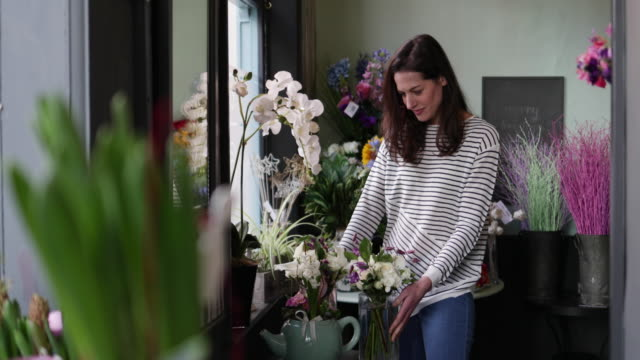 adult female choosing flowers in a florist - florist stock videos and b-roll footage