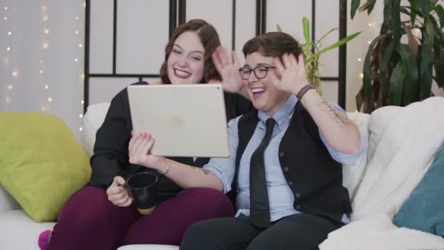 Adulte Couple féminin s'adressant à quelqu'un sur une tablette numérique