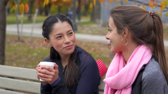 adult female friends drinking coffee on a park bench - park bench stock videos & royalty-free footage