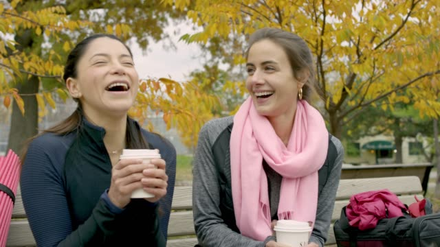 adult female friends drinking coffee on a park bench - bench stock videos & royalty-free footage