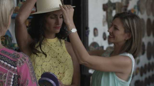 Adult Female Friends shopping and fitting hats in boutique