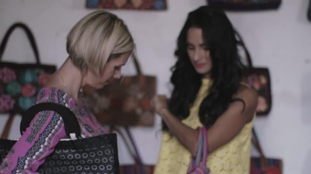 vídeos de stock, filmes e b-roll de adult female friends shopping for handbags - bolsa tiracolo bolsa