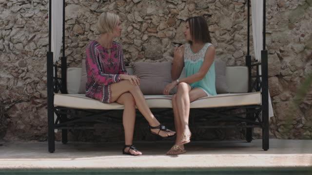 Adult Female Friends talking on sofa in garden