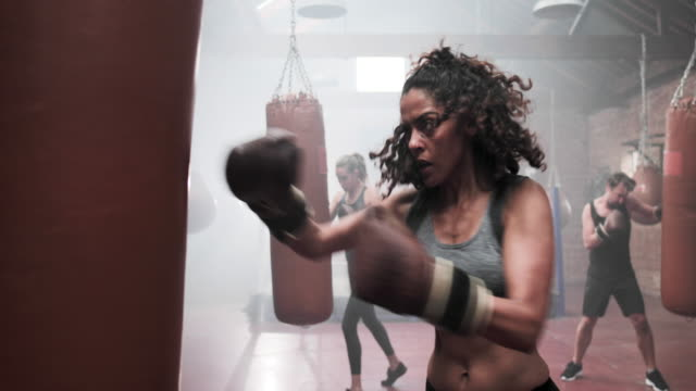 adult female in a boxing fitness class - punch bag stock videos & royalty-free footage