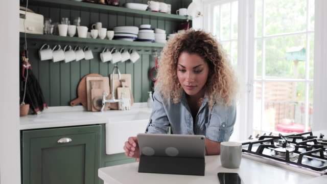 adult female looking at digital tablet whilst having morning coffee - film moving image stock videos & royalty-free footage