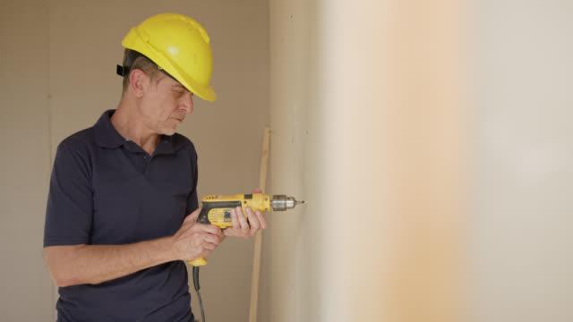 建設現場で木製の壁を掘削する大人の職長 - ドリル点の映像素材/bロール