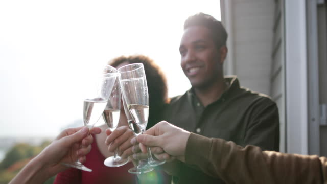 stockvideo's en b-roll-footage met adult friends enjoying a glass of champagne outdoors in sunshine - feest en gedenkdagen